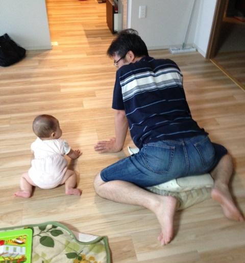 赤ちゃんのハイハイをサポートするパパ